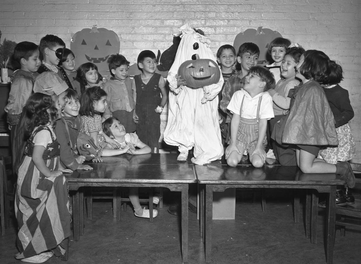 Children at school on Halloween with one student dressed up as a pumpkin ghost standing in the middle