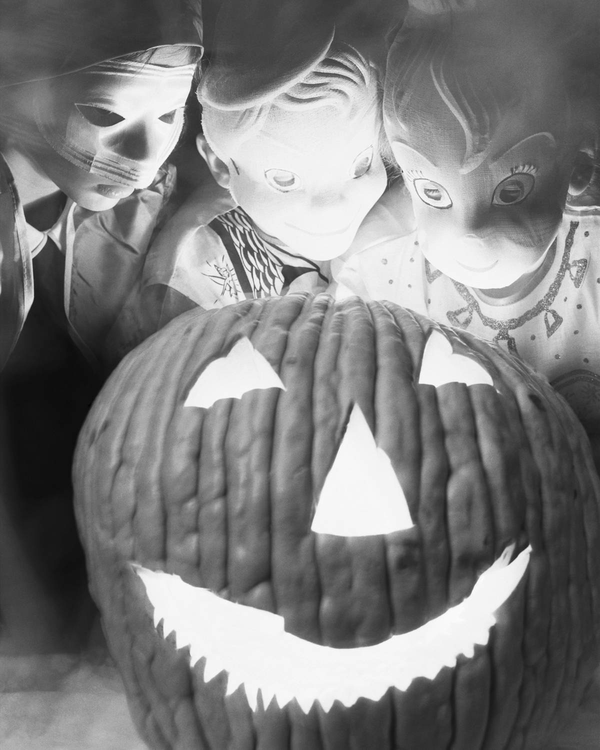 Children dressed as goblins surround a jack-o'-lantern in a photo from 1953