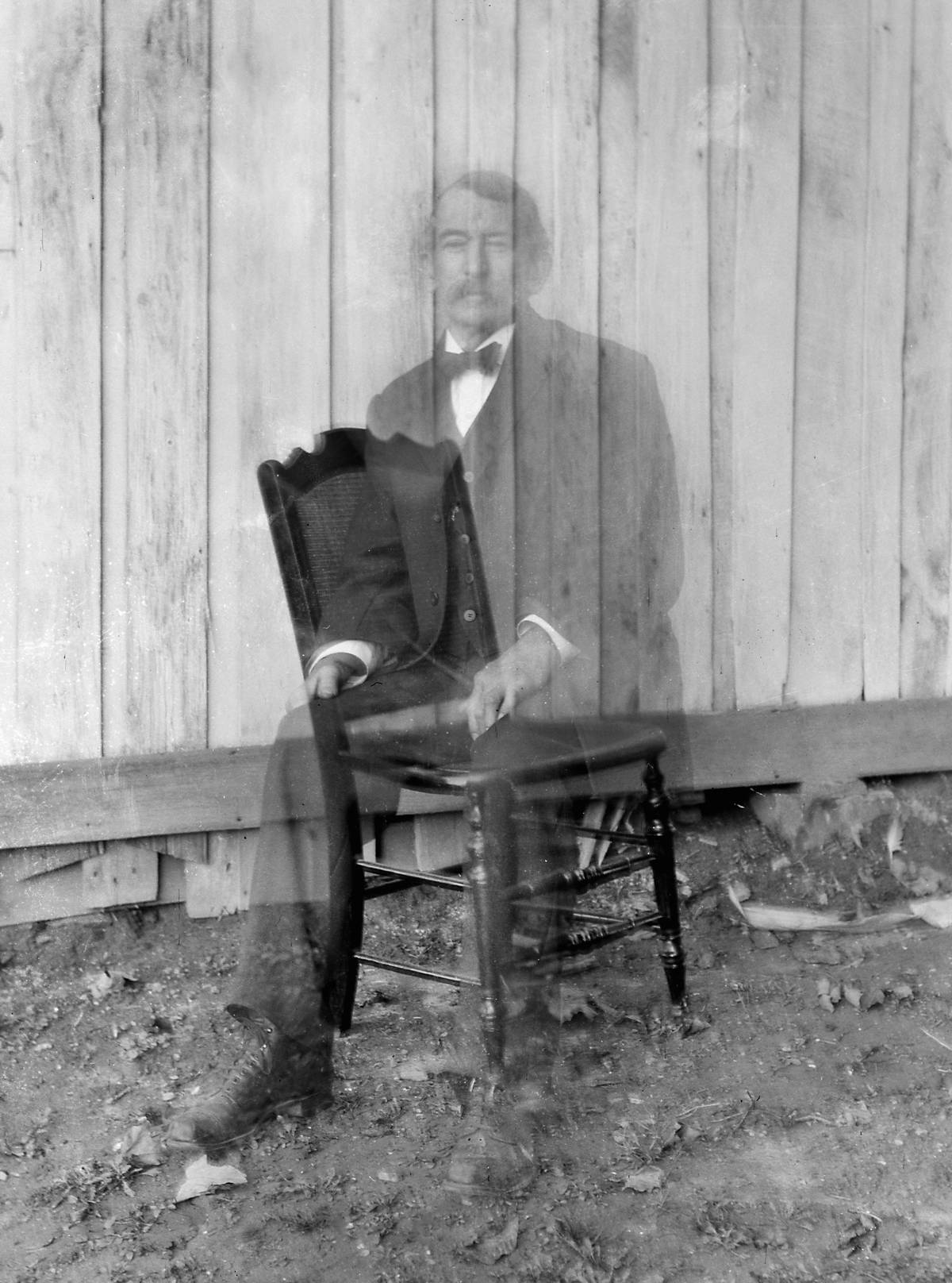 Double exposure of a man sitting on a chair making it look like he's a ghost from 1900