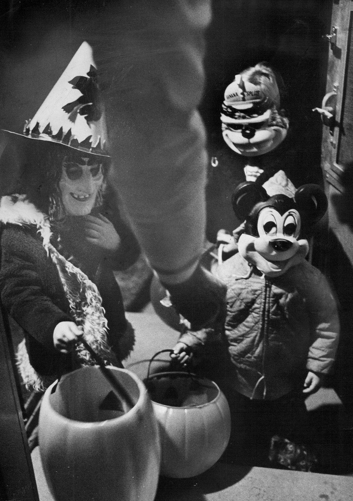 A small group of children wear costumes and masks and walk house to house trick-or-treating on Halloween