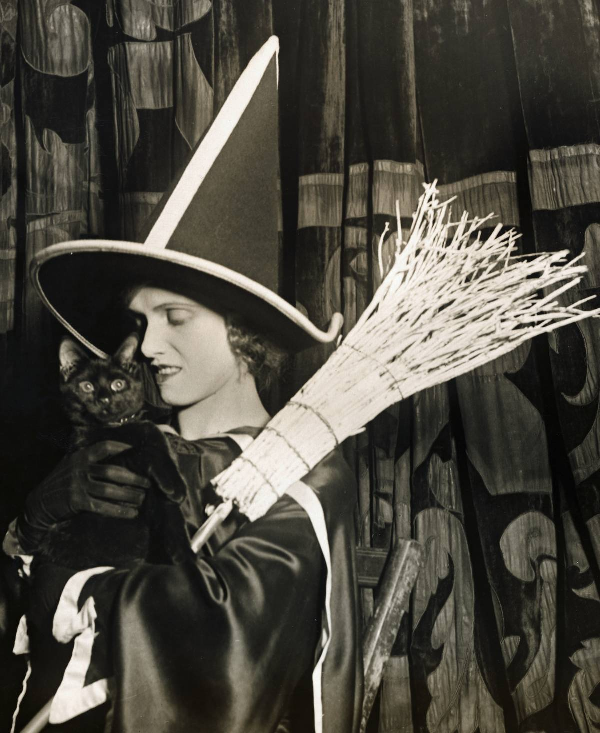 A woman wearing a witch costume, holding a straw broom and a black cat
