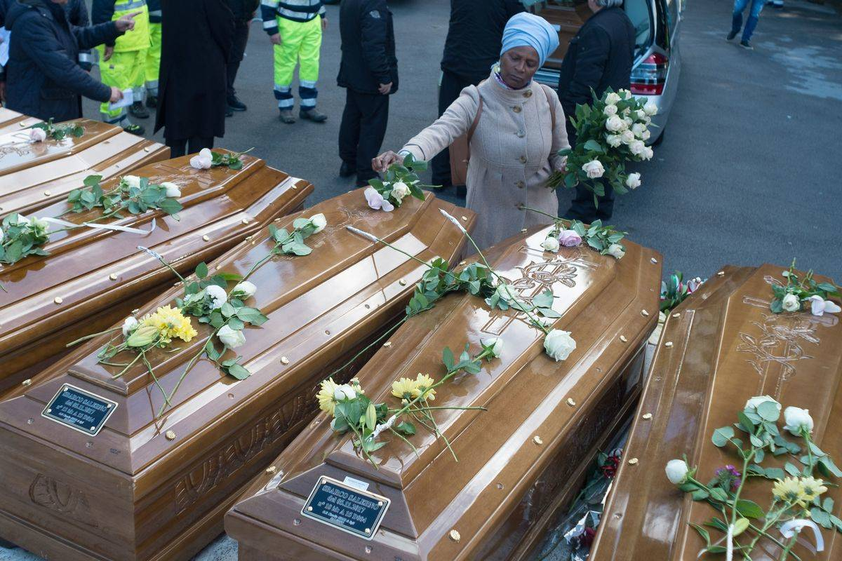 A woman lays flowers on coffins placed next to each other.