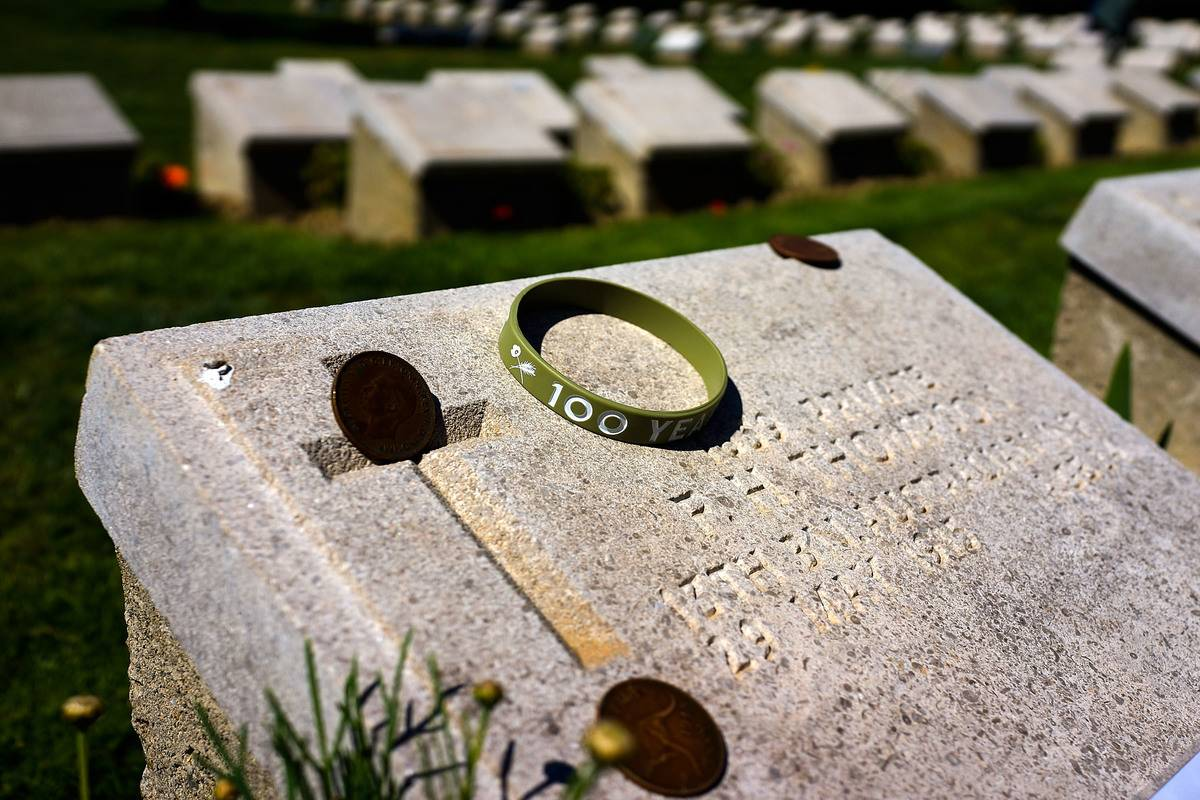 A few coins and a bracelet are on top of a grave.