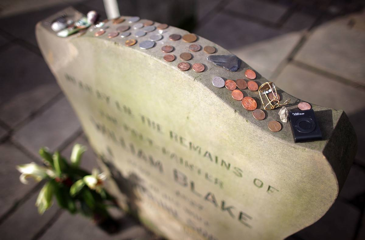 Coins have been placed on a poet's headstone.
