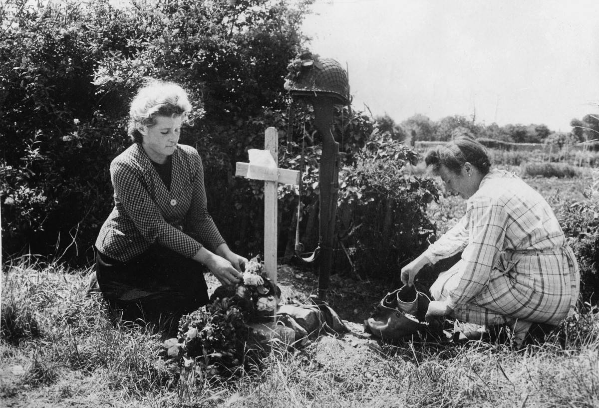 During World War II, two women decorate a grave.