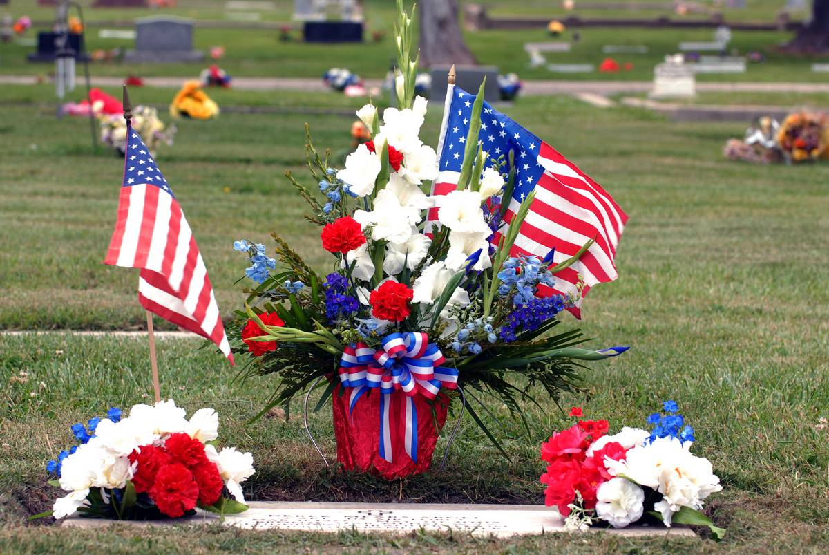 A bouquet is arranged with an American flag at a cemetery.
