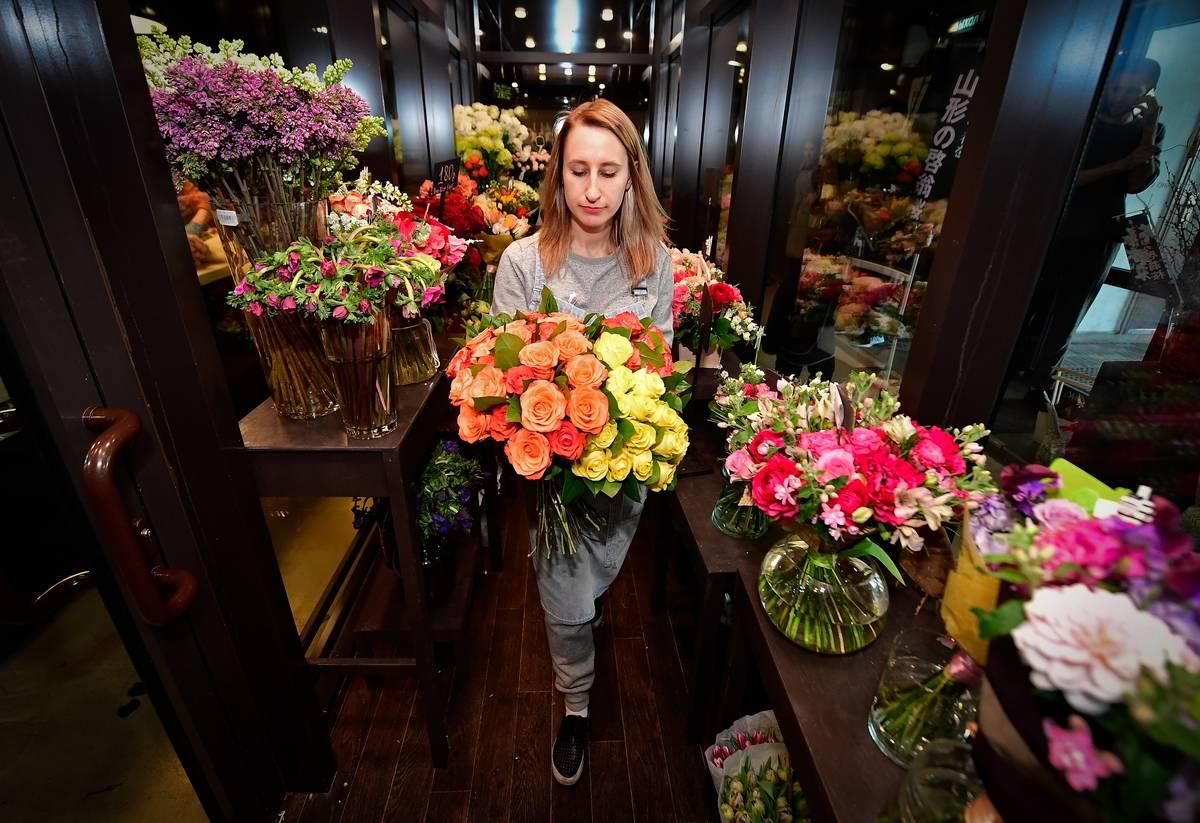 A florist carries a bouquet through her shop.