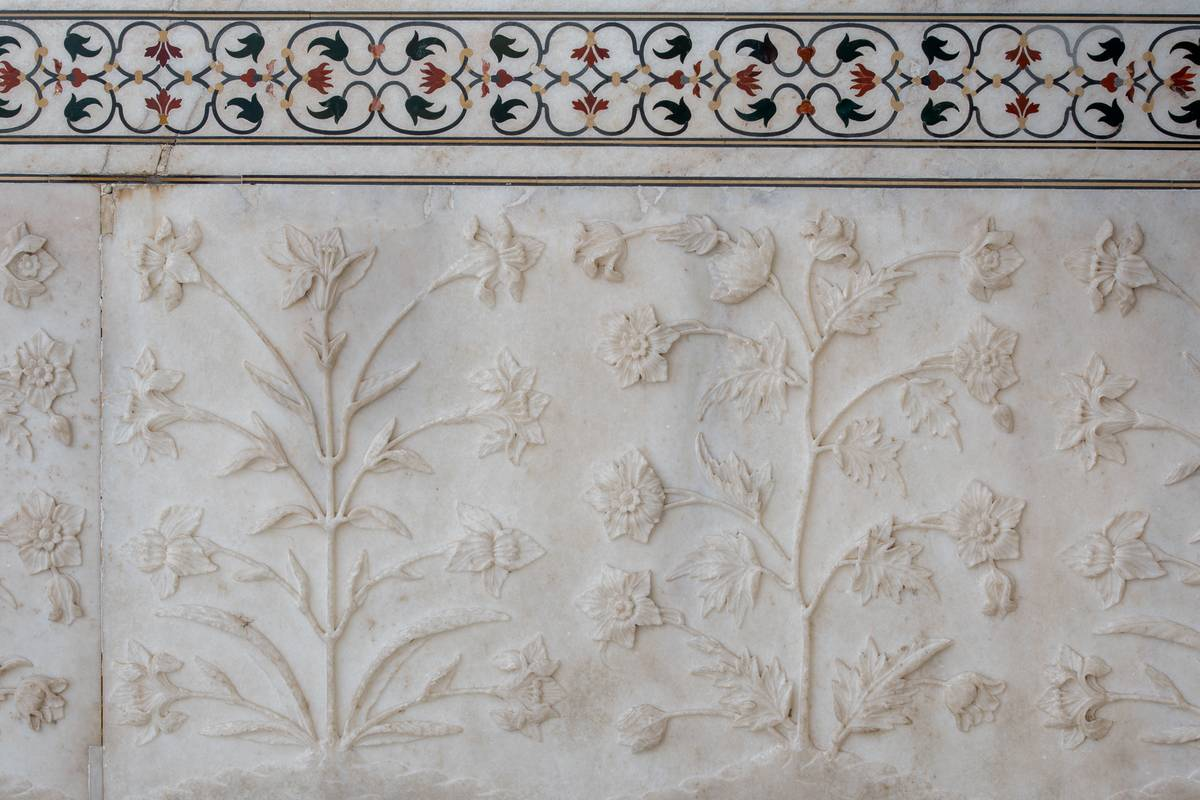 A delicate floral relief sculpture on the ivory marble walls of the Taj Mahal.