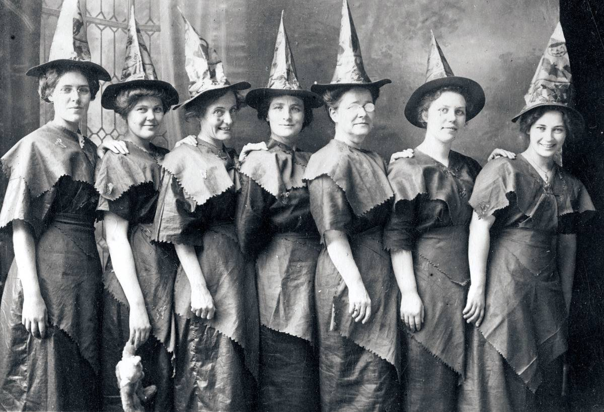 A group of women dressed up as witches in a photo from 1910