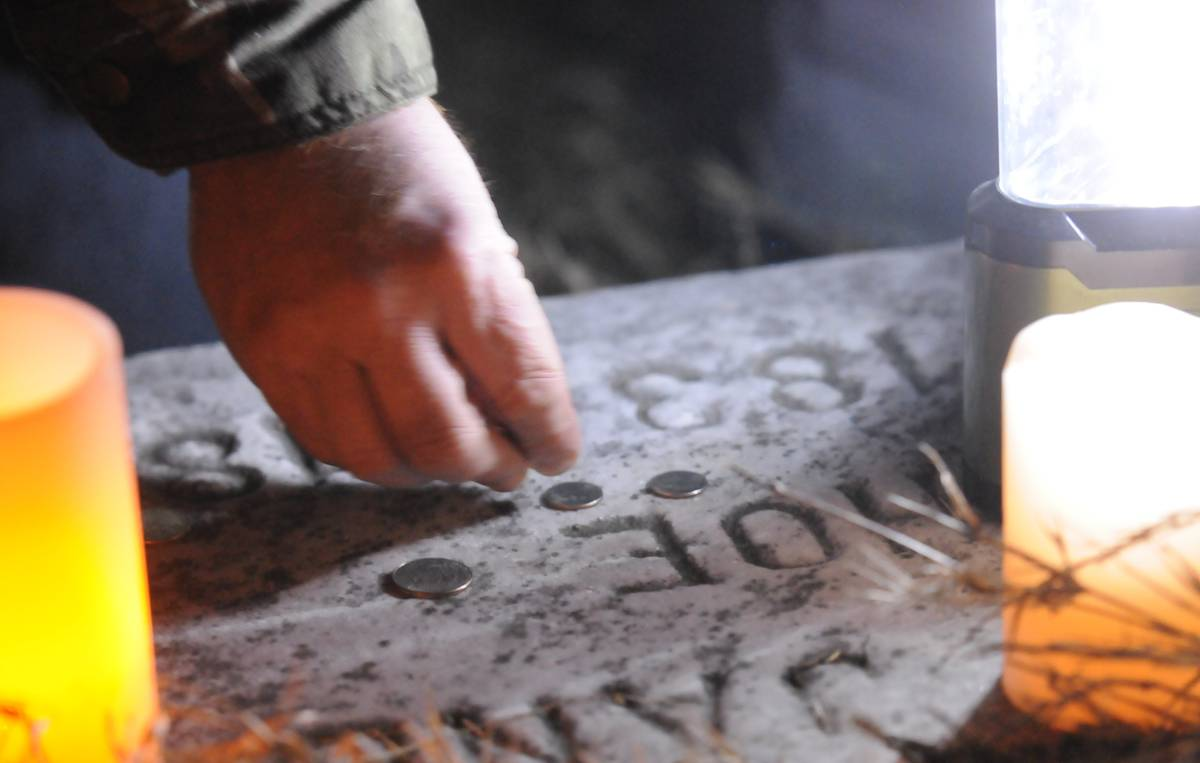 A visitor places coins on a grave marker.