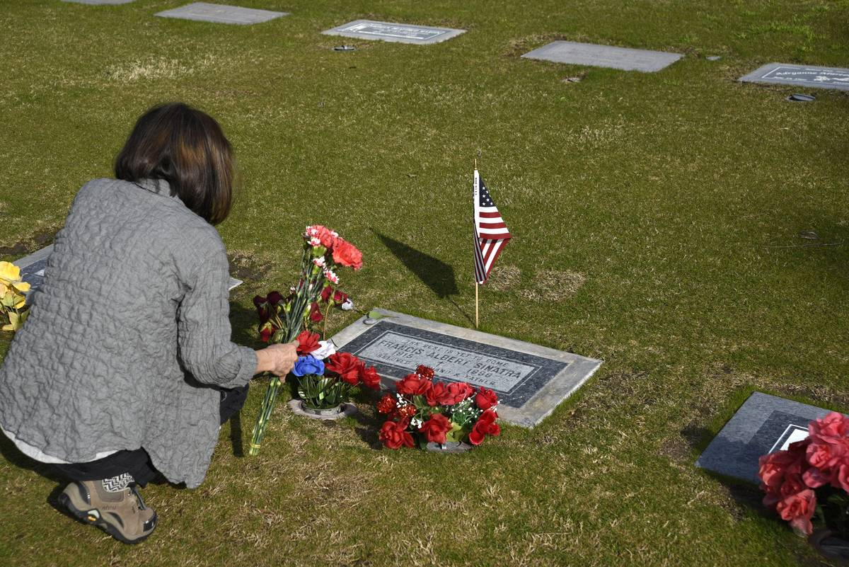 A woman places flowers on Frank Sinatra's grave.