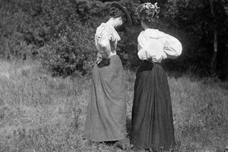 Two young women in Victorian dress talking privately with their backs to the camera