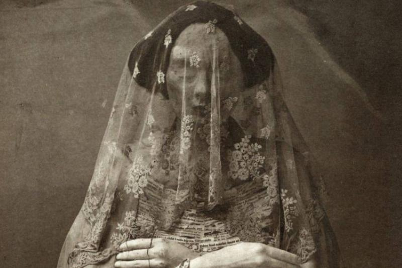 a figure with a head covering in victorian clothes